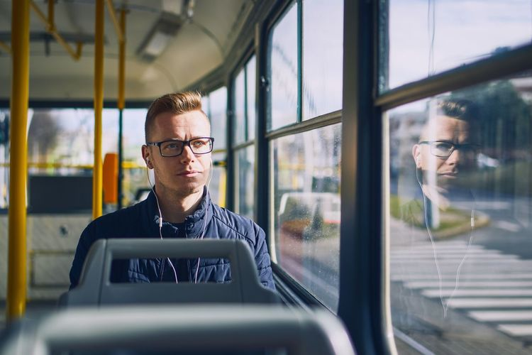 Young man listening music in tram. Travel by public transportation. Tram Tramway Public Transportation Transportation City City Life Men Travel Commuting Connection Communication Headphones Listening Listen Music Real People Mode Of Transportation Reflection Young Adult Young Men Eyeglasses  Window Inside Contemplation Lonely