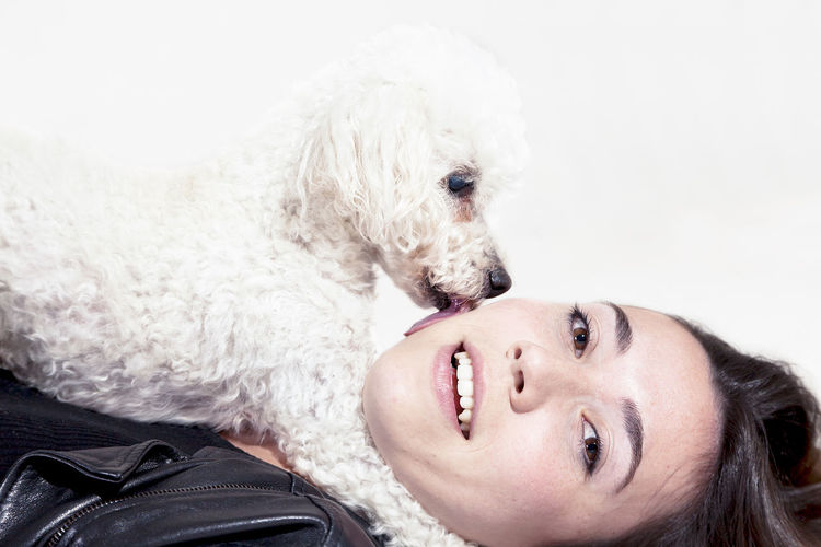 Young woman with dog against white background