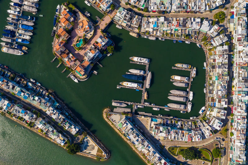 Aerial view of boats moored by cityscape