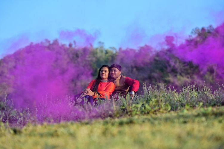 Man And Woman Sitting On Field Against Sky