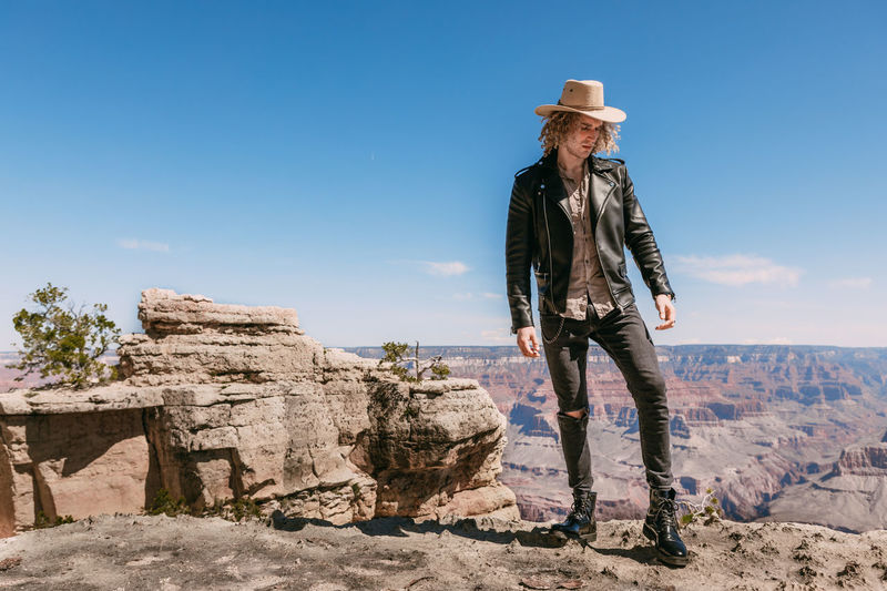 Full length of man wearing hat standing on cliff against sky