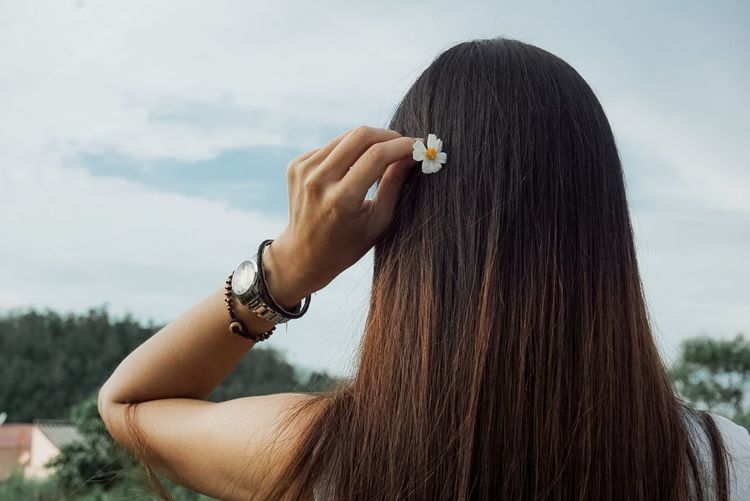 Rear view of woman putting flower in hair against sky