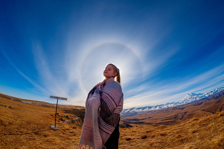 Full length of woman standing on land against sky and halo