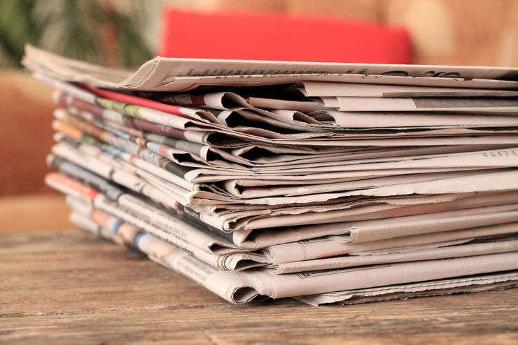 Stack of newspapers on wooden table