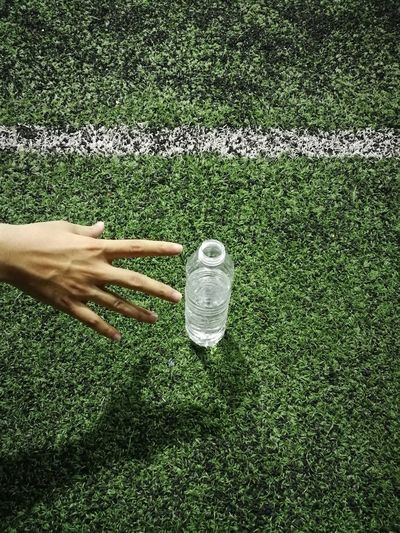 Cropped Hand Reaching For Water Bottle On Playing Field