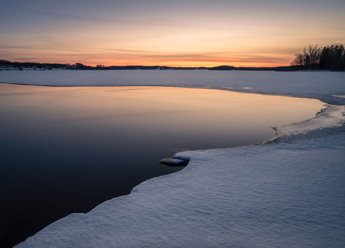 Scenic winter landscape with lake reflections and sunset at evening in Finland Calm Finland Moment Of Silence Reflection Tranquility Travel Twilight Atmospheric Mood Beauty In Nature Cold Temperature Frozen Ice Lake Melted Nature No People Scenics - Nature Sky Snow Sunrise Sunset Tranquil Scene Tranquility Water Winter