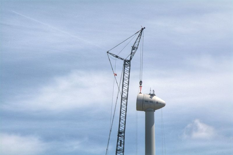 Low Angle View Of Crane And Windmill Against Cloudy Sky