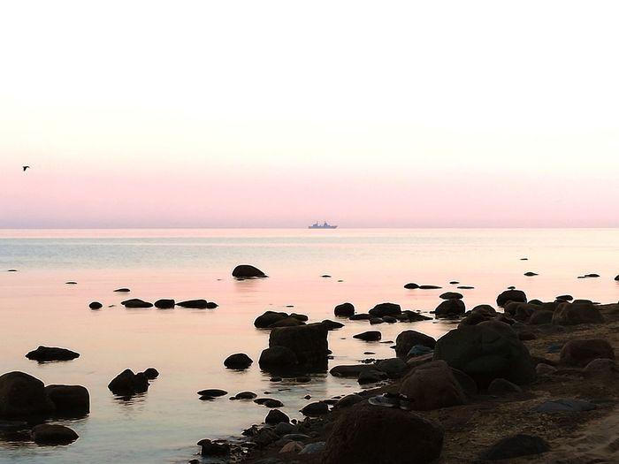 The ship on the bay Water Sea Sunset Beach Silhouette Sunlight Sun Blue Rock - Object Dusk Romantic Sky Tide Low Tide Atmospheric Mood