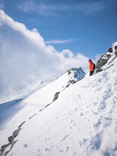 Low Angle View Of Person Standing On Snowy Mountain Against Cloudy Sky