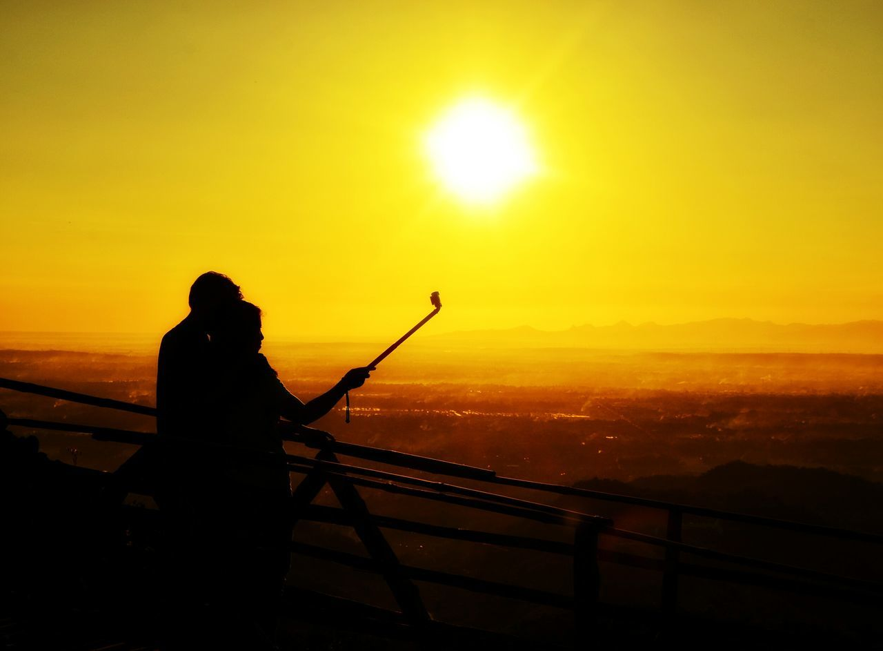 sunset, orange color, silhouette, sun, nature, real people, one person, scenics, beauty in nature, sky, outdoors, tranquil scene, leisure activity, men, sunlight, tranquility, lifestyles, standing, water, day, people