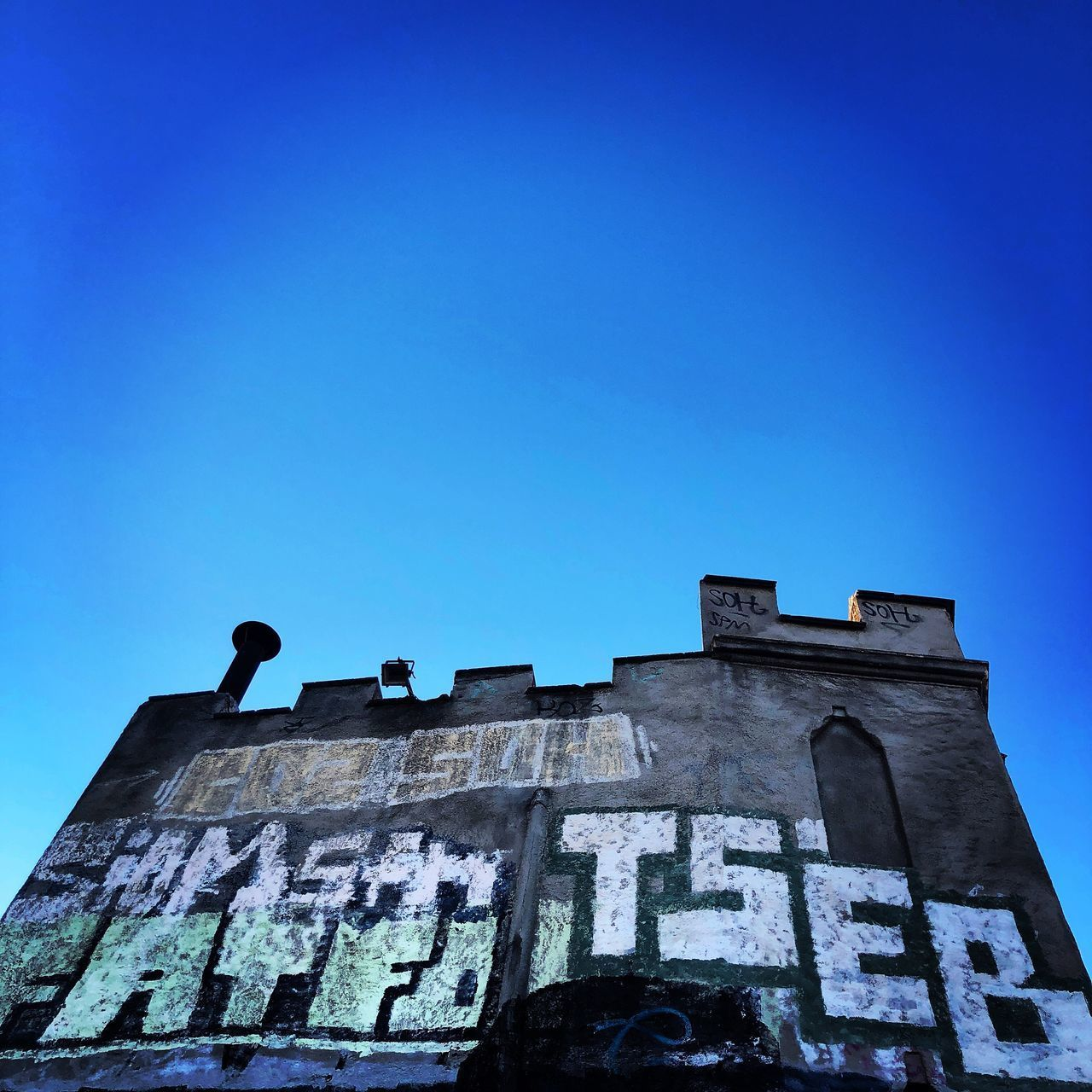 sky, low angle view, building exterior, clear sky, architecture, built structure, blue, copy space, nature, building, day, no people, history, old, the past, outdoors, residential district, abandoned, run-down, wall - building feature