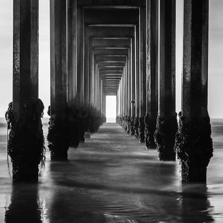 Under The Boardwalk Tunnelvision Monochrome Ocean Under The Pier Under The Pier And Ocean Blackandwhite Water Architectural Column Indoors  Day Architecture No People Nature