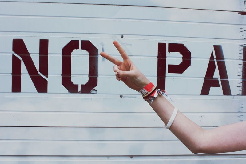 Cropped Hand Of Woman Gesturing Peace Sign Against Shutter