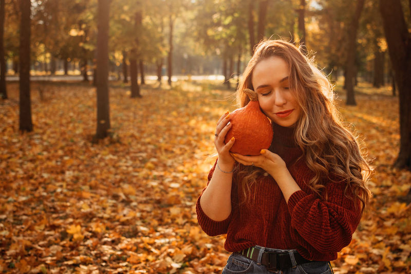 Young beautiful smiling woman with long curly hair holding orange halloween pumpkin on autumn park