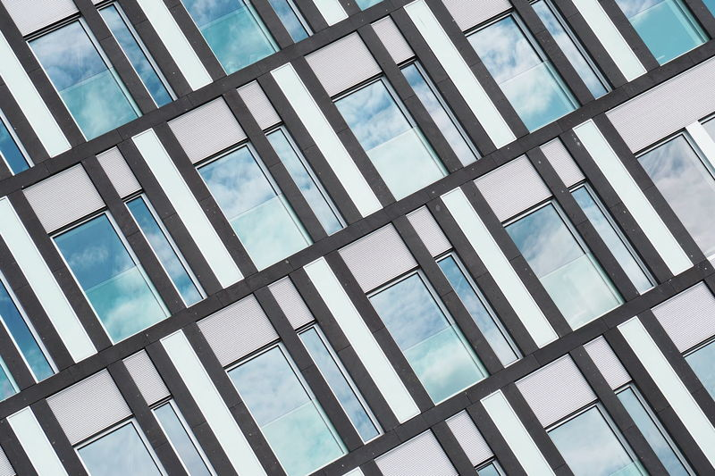 Low angle view of glass window against sky