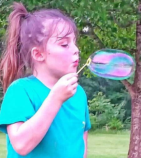 Child Playing With Bubbles Child Photography Girl Having Fun Outdoor Play Bubbles Big Bubble Rainbow Colors In Bubble Playing Outside Natural Light Photo Natural Light Portrait