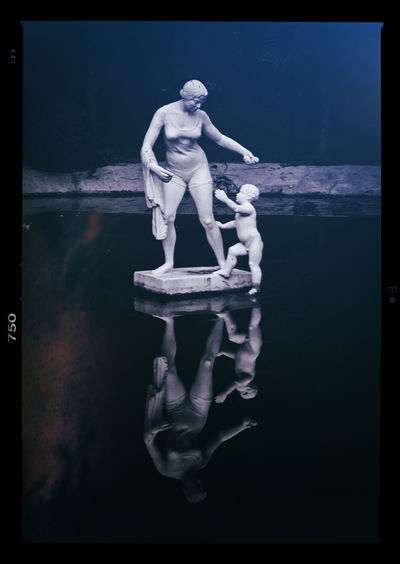 Digital composite image of statue by sea against black background