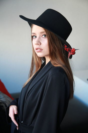Portrait of beautiful woman wearing hat standing against wall