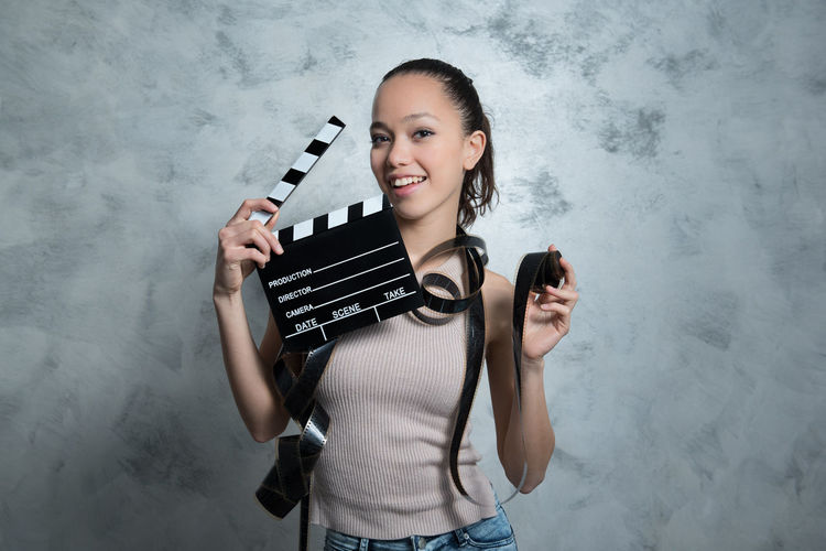 Close-Up Portrait Of Woman Holding Film Slate