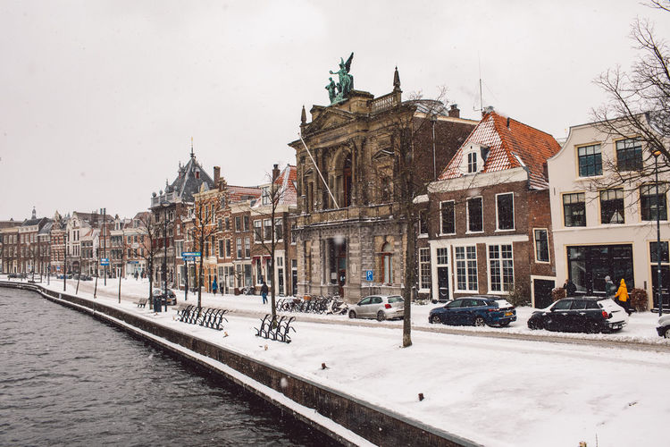 Buildings in city against sky during winter