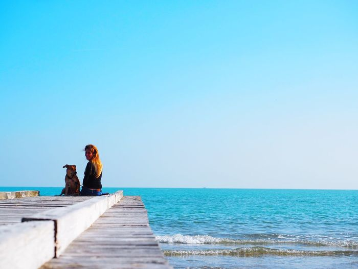 Girl and her puppy sitting on beach against clear blue sky
