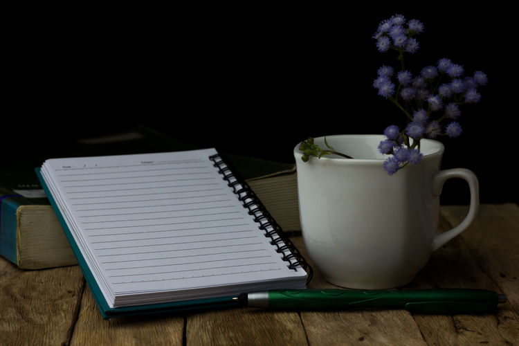 Close-up of flowers in cup by spiral notebook on wooden table against black background