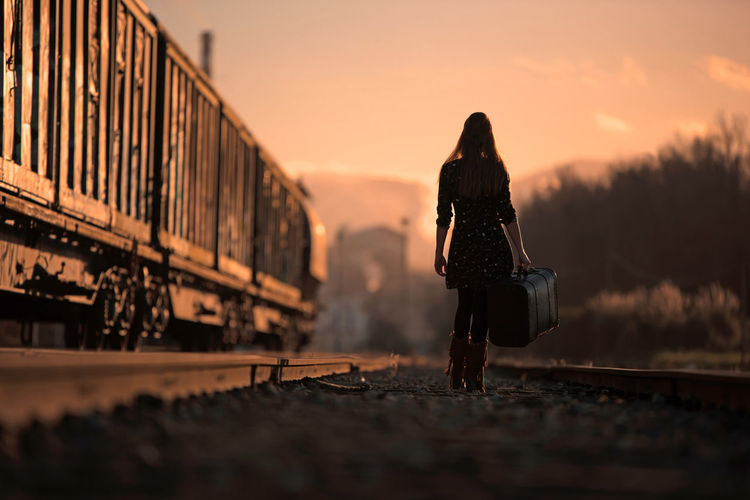 Rear view of woman standing on train at sunset