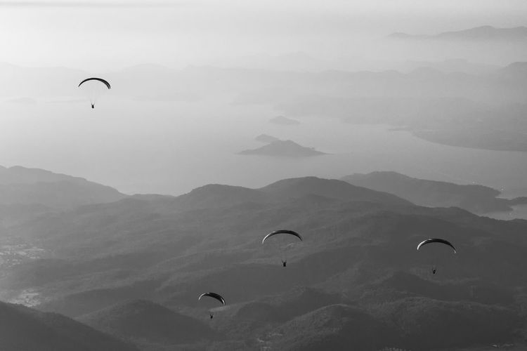 Silhouette people paragliding over mountains