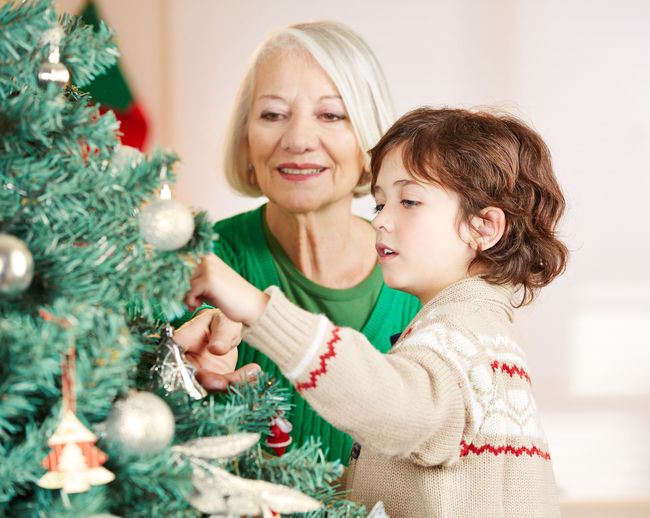 Smiling Grandmother Looking At Son Decorating Christmas Tree