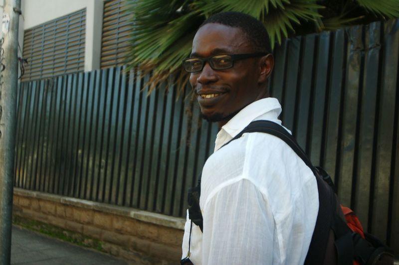 Portrait of smiling man walking on sidewalk in city
