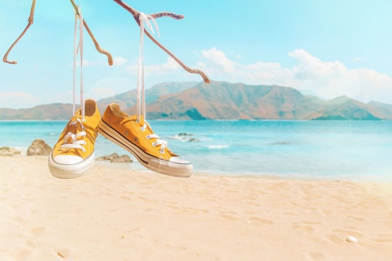 Yellow canvas shoes hanging from branch at beach against sky