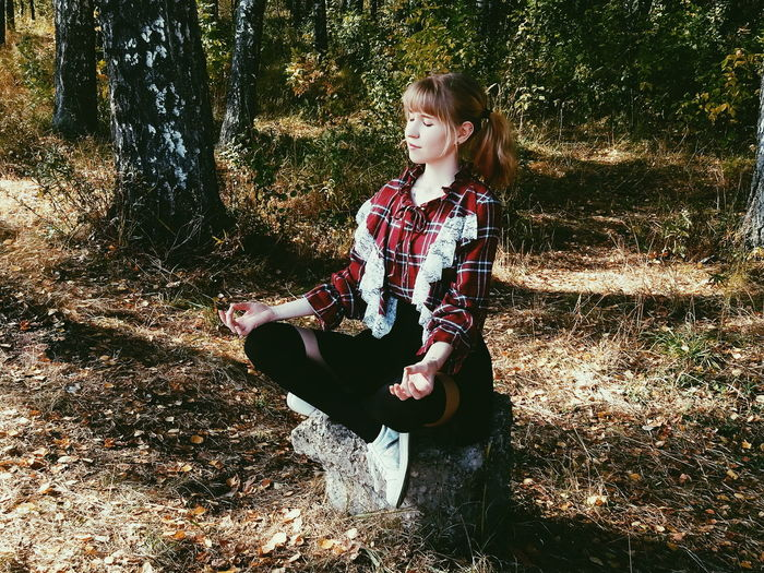 Young woman meditating while sitting in forest