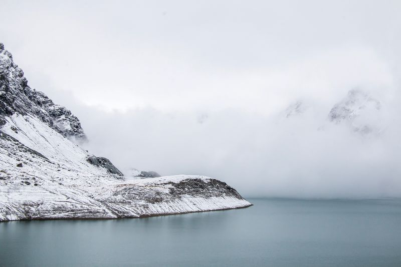 Scenic view of snow covered mountain by sea against sky
