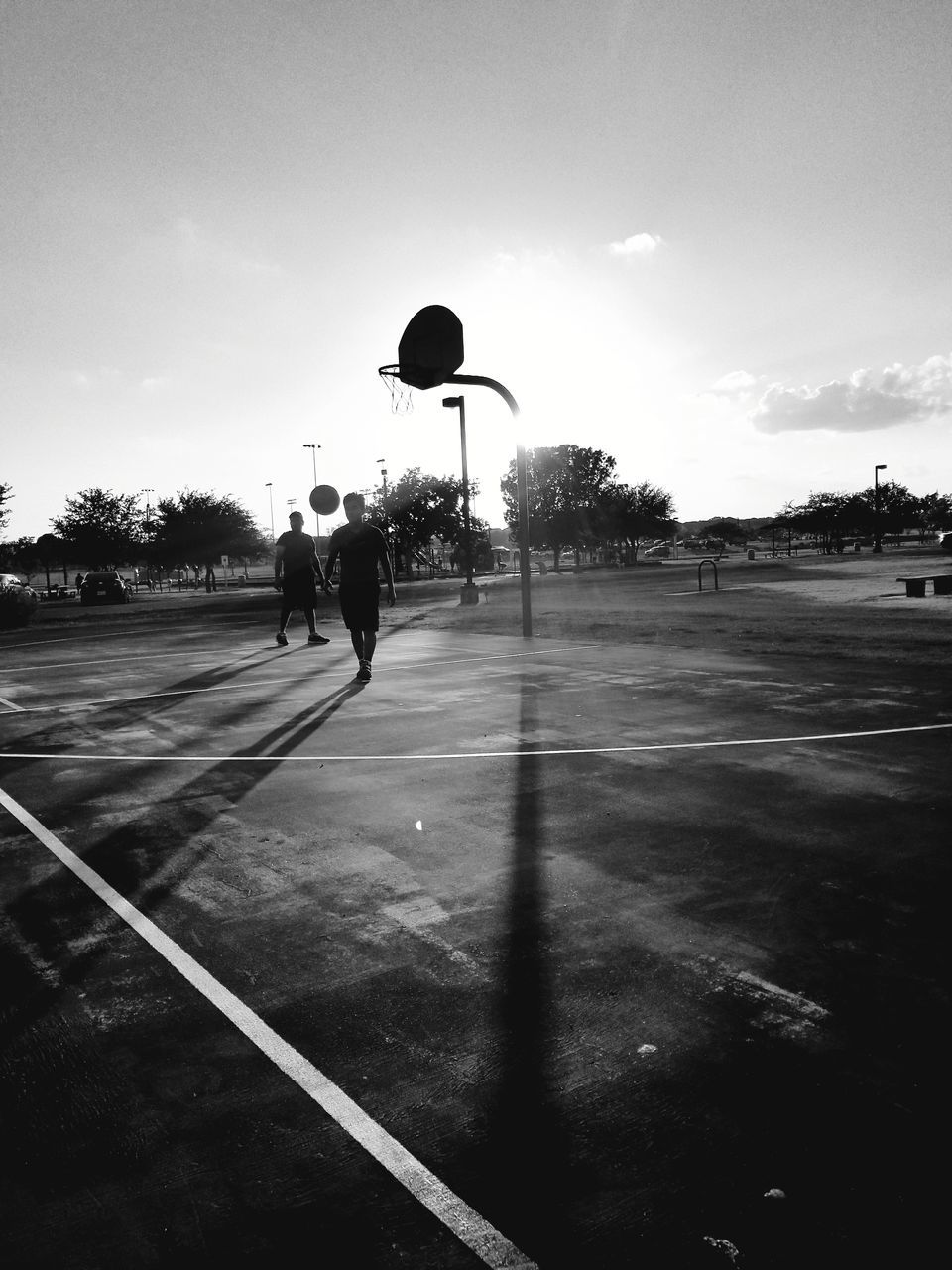Players Playing At Basketball Court In Sunny Day