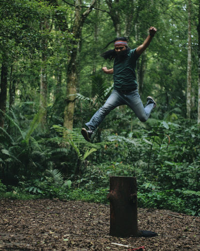 Full length of young man jumping in forest