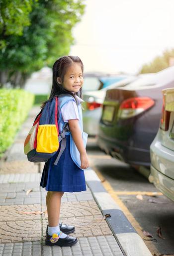 Portrait of cute smiling girl wearing school uniform standing on footpath