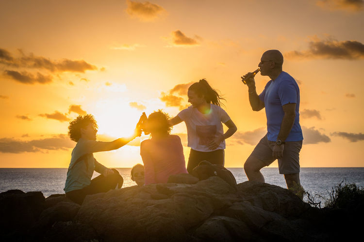 People on rock at beach against sky during sunset