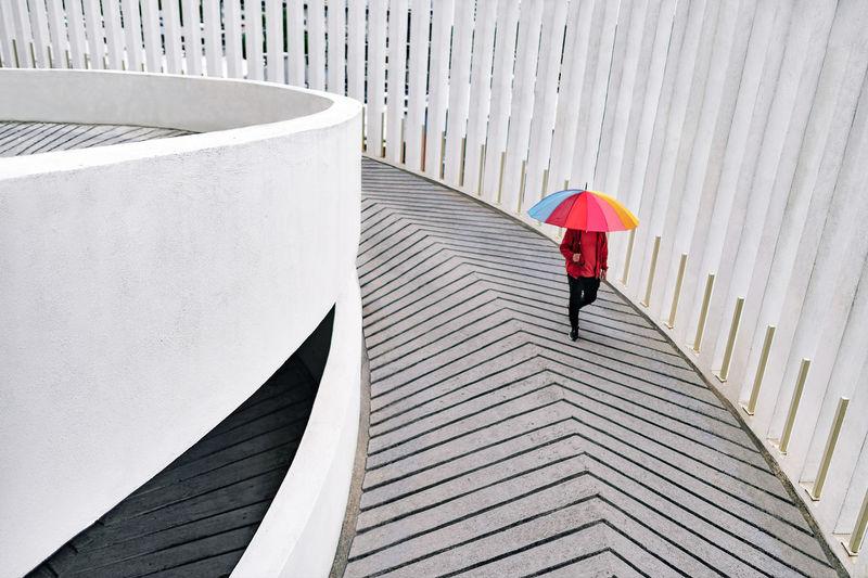 A man walking with an umbrella down the carpark ramp