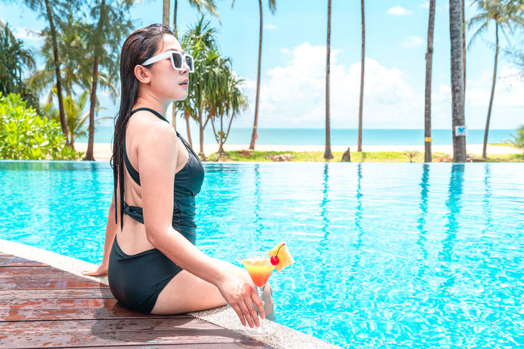 Side view of young woman sitting in swimming pool