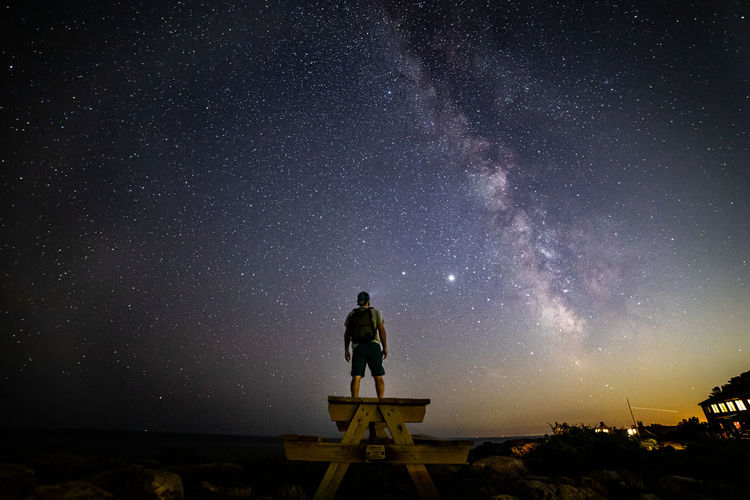 Man standing against sky at night