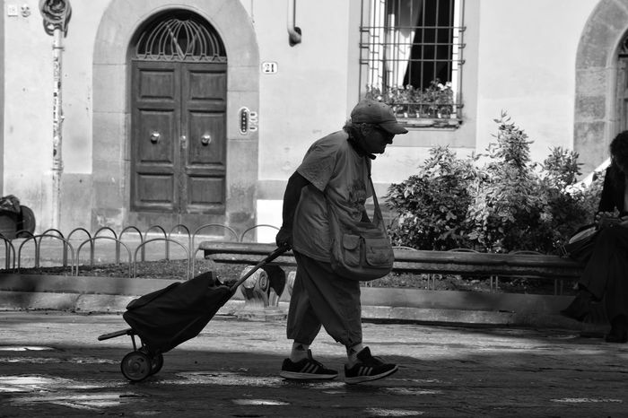 One Person Adults Only Elderly Woman Shopping Shopping Cart People Watching Street Photography Black And White Monochrome Shadows & Lights Real People Italy Visit Italy Florence Warm Clothing Day Outdoors Full Length Street Shapes And Forms City Walk Door The Week On EyeEm