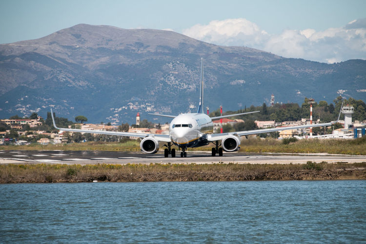 Airplane at airport runway against mountains