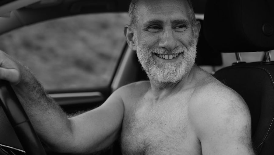 Monochrome of portrait of shirtless adult man smiling in car