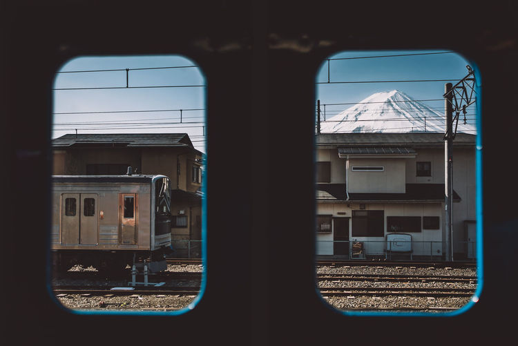 Train and snowcapped mountain seen through window