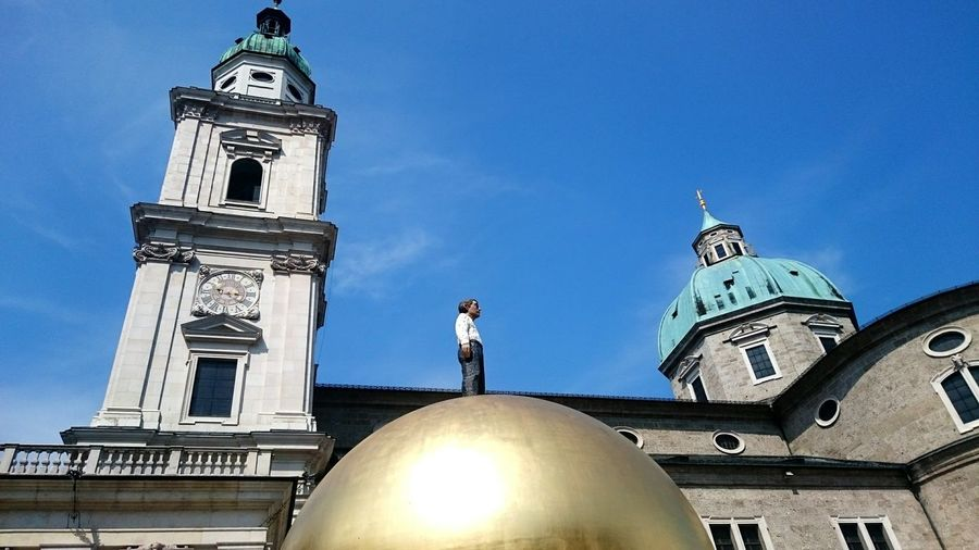Low angle view of male statue on gold colored dome against salzburg cathedral