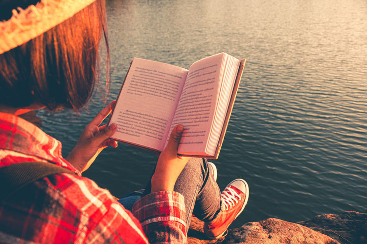 Low section of woman reading book in lake