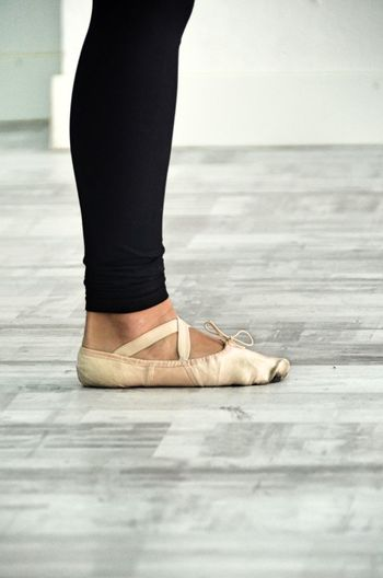 Low section of woman wearing ballet shoe standing on floor