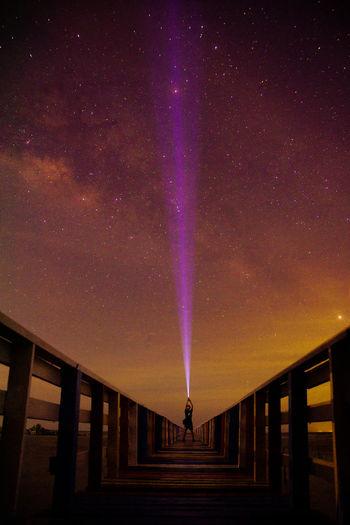 Man standing on illuminated railing against sky at night