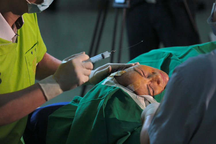 Cropped Hands Of Doctor Injecting Syringe To Patient In Operating Room