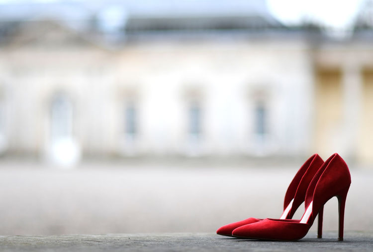 Close-up of red shoes on table against building